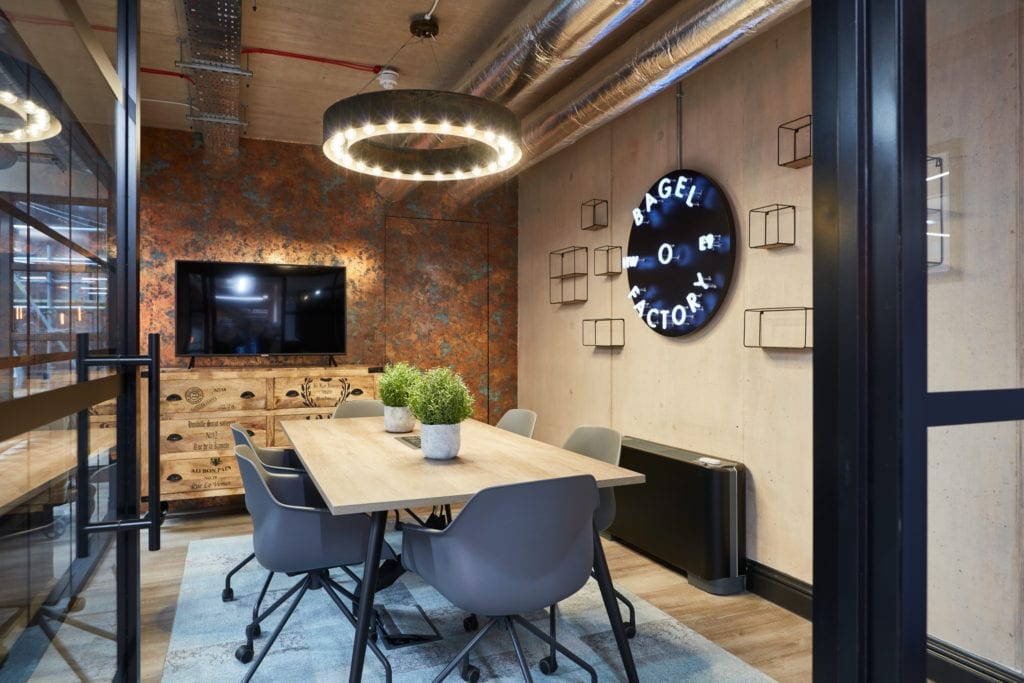 Office meeting room refurbishment with television, table and branded lighting features.