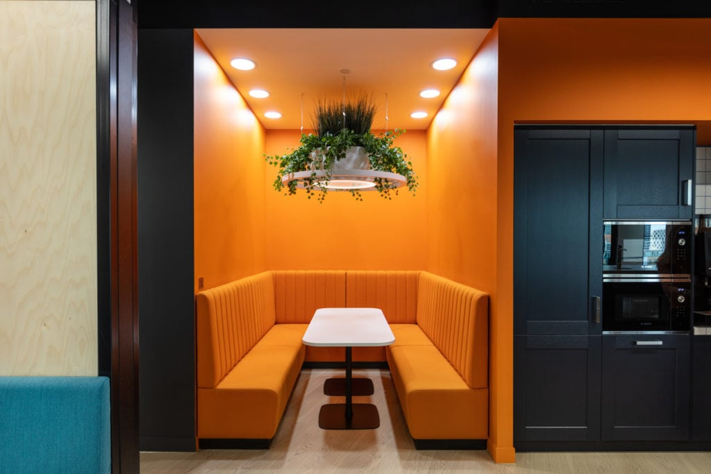 Workplace refurbishment with orange seating booth with hanging plant light feature next to office kitchen area.