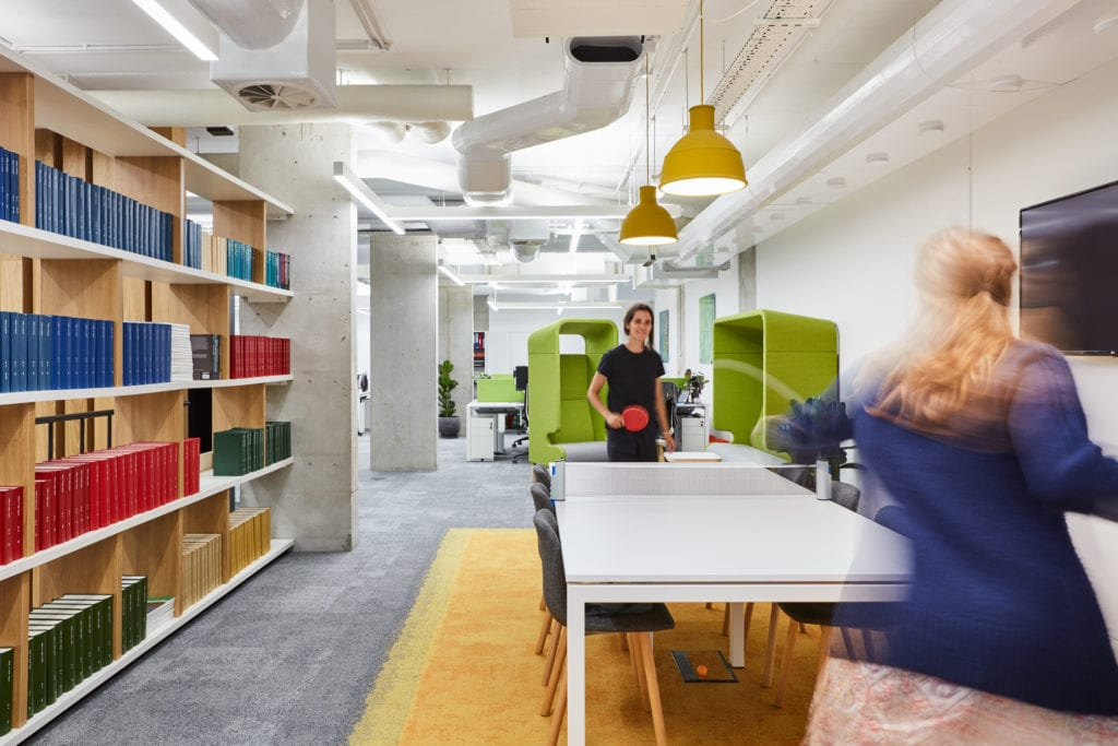 Office break out space refurbishment with large bookshelf, seating area and two employees playing table tennis.