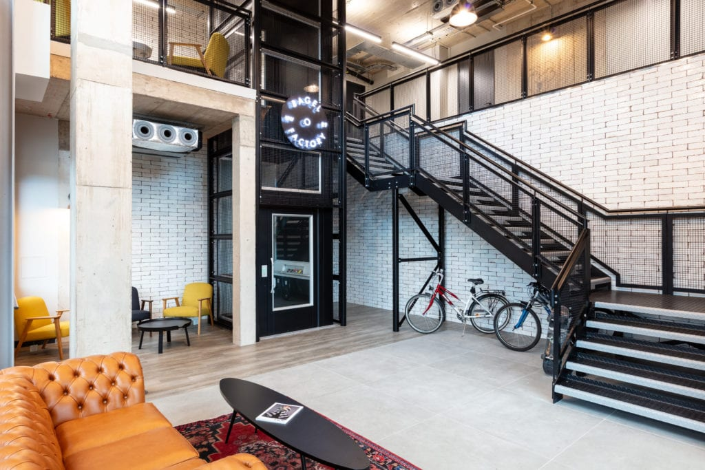 Workspace stairwell with branded lighting graphic, wheelchair access lift, seating area, sofa, coffee table and bikes stored under the stairs.