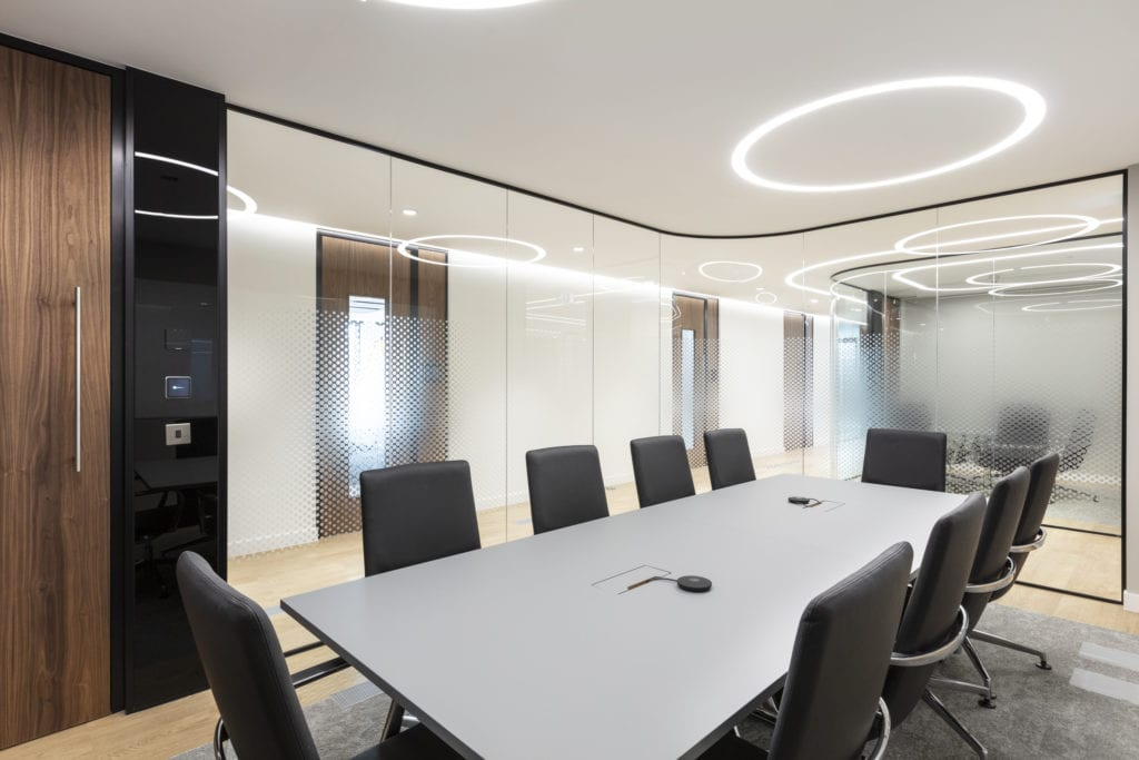 Workplace meeting room with circular track lighting on ceiling.